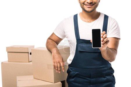 Photo pour Vue recadrée de déménageur indien heureux en salopettes tenant smartphone avec écran vide près de boîtes en carton isolé sur blanc - image libre de droit