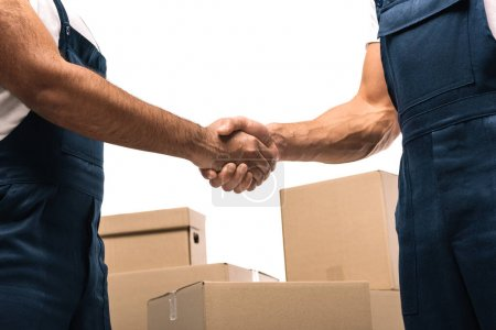 cropped view of movers shaking hands near boxes isolated on white