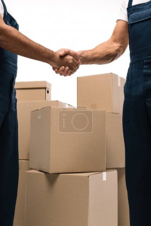 cropped view of handymen shaking hands near boxes isolated on white