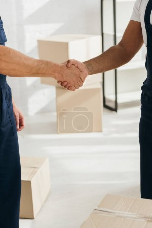 Photo for Partial view of workers shaking hands in apartment - Royalty Free Image