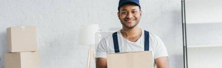 Photo pour Joyeux coursier indien en casquette et uniforme boîte de maintien dans l'appartement, bannière - image libre de droit