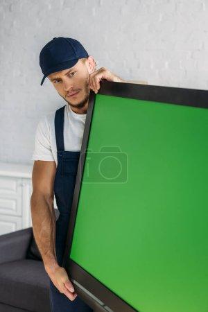 Photo pour Jeune déménageur en uniforme portant la télévision à écran plasma avec écran vert dans l'appartement - image libre de droit