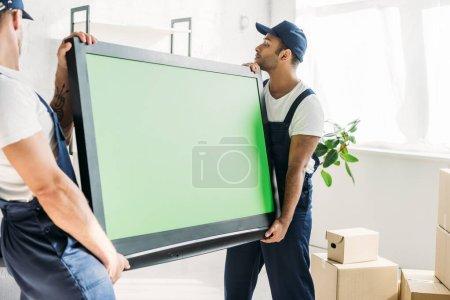 Photo pour Déménageurs multiculturels en casquettes et uniforme portant TV plasma avec écran vert dans l'appartement - image libre de droit