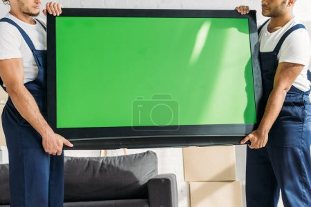Photo pour Vue recadrée des déménageurs multiculturels en uniforme portant la télévision à écran plasma avec écran vert dans l'appartement - image libre de droit