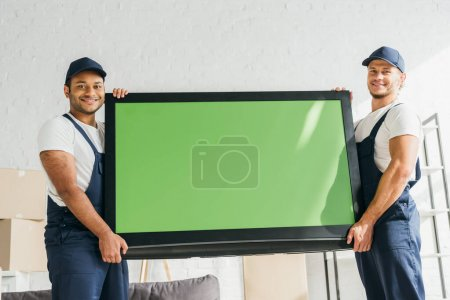 Photo pour Déménageurs multiculturels souriants en uniforme portant la télévision à écran plasma avec écran vert dans l'appartement - image libre de droit