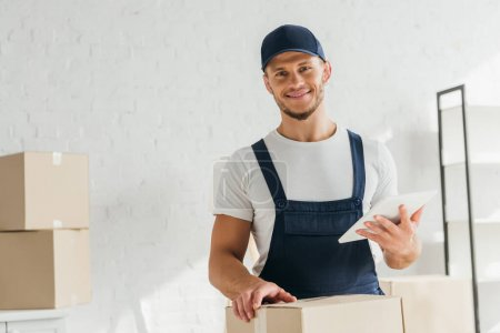 cheerful mover in uniform holding digital tablet near boxes in apartment