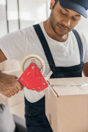 Photo for Indian mover in uniform packing box in apartment - Royalty Free Image