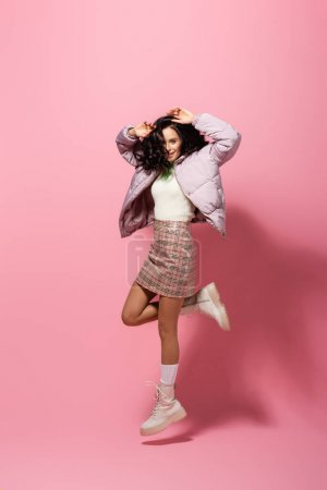 Photo pour Brunette jeune femme en tenue d'hiver élégant sautant sur fond rose - image libre de droit