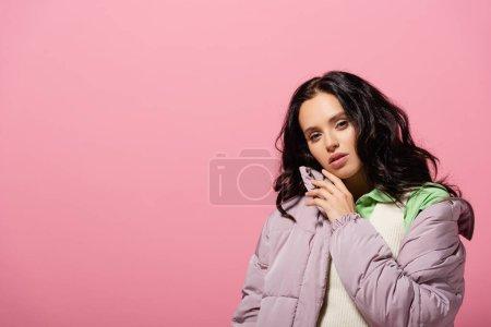 Photo pour Brunette jeune femme en tenue d'hiver sur fond rose - image libre de droit