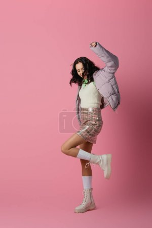 happy brunette young woman in stylish winter outfit dancing on pink background