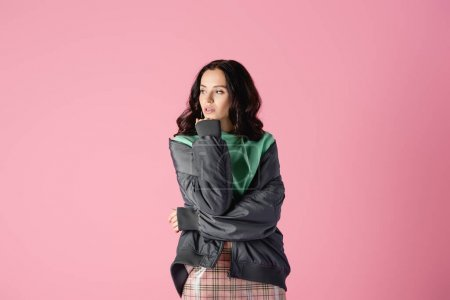 smiling brunette young woman in casual winter outfit posing on pink background