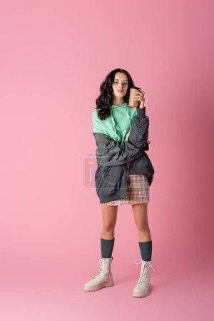 Photo pour Brunette jeune femme en tenue d'hiver décontractée avec tasse en papier sur fond rose - image libre de droit
