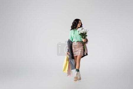 Photo pour Jeune femme brune souriante en tenue d'hiver élégante posant avec des fleurs et des sacs à provisions sur fond gris - image libre de droit