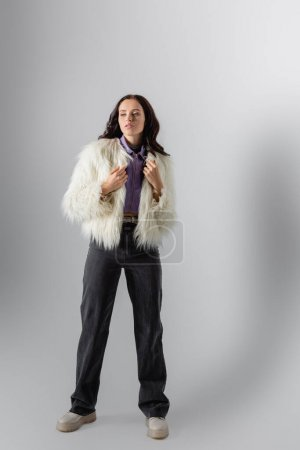 brunette young woman in stylish white faux fur jacket posing on grey background