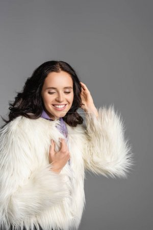 smiling elegant brunette young woman in stylish white faux fur jacket posing on grey background