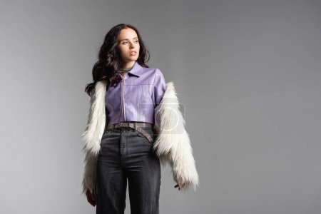 Photo pour Elegant brunette young woman in stylish white faux fur jacket posing on grey background - image libre de droit