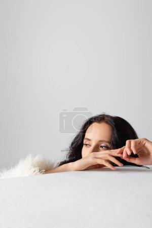 Photo pour Élégante jeune femme brune veste en fausse fourrure derrière cube sur fond blanc - image libre de droit