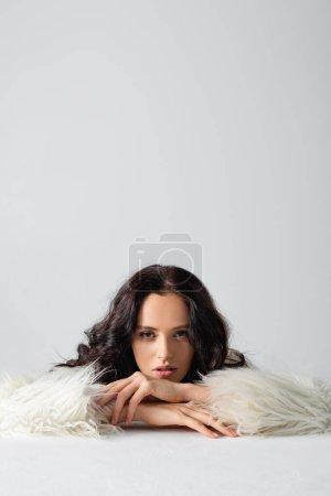 Photo pour Élégante jeune femme brune veste en fausse fourrure posant près du cube sur fond blanc - image libre de droit