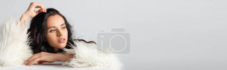 elegant brunette young woman in faux fur jacket posing near cube on white background, banner