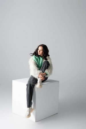 Photo for Brunette young woman in faux fur jacket posing on cube on white background - Royalty Free Image