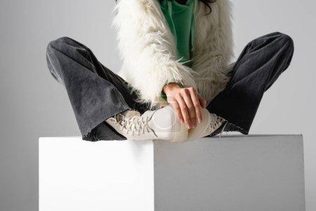 Photo pour Vue recadrée de la jeune femme en fausse fourrure veste et bottes posant sur cube sur fond blanc - image libre de droit