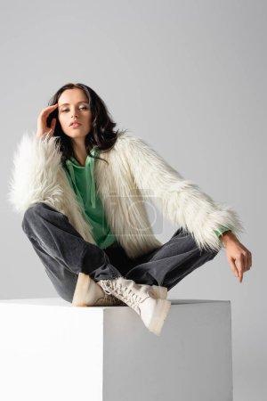 Photo pour Brunette jeune femme en fausse fourrure posant sur cube sur fond blanc - image libre de droit