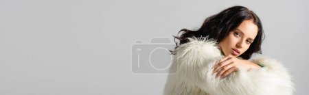 brunette young woman in faux fur jacket posing on white background, banner