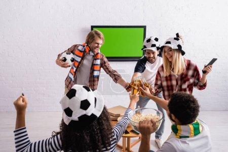 Photo pour Amis multiethniques joyeux dans les fans de football chapeaux bouteilles de bière près de lcd tv sur le mur - image libre de droit