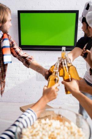 Photo pour Fans de football multiethnique clinquant bouteilles de bière tout en regardant le championnat à la télévision près de pop-corn sur fond flou - image libre de droit