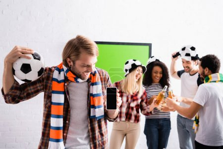 cheerful man holding soccer ball and smartphone with blank screen near multiethnic friends clinking bottles of beer on blurred background
