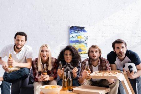 Photo pour Amis multiethniques inquiets regardant la compétition de football avec de la bière, des chips et des pizzas à la maison - image libre de droit