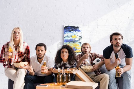 focused multiethnic football fans watching championship with beer and snacks at home