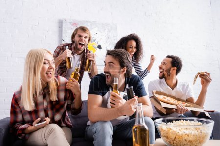 excited sports fans holding bottles of beer while watching competition at home