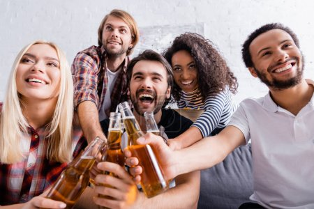 Photo pour Amis multiethniques excités accrochant des bouteilles de bière au premier plan flou pendant la fête, au premier plan flou - image libre de droit