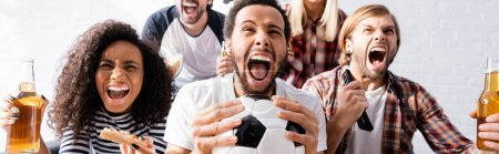 excited multiethnic friends screaming while watching football championship at home, banner
