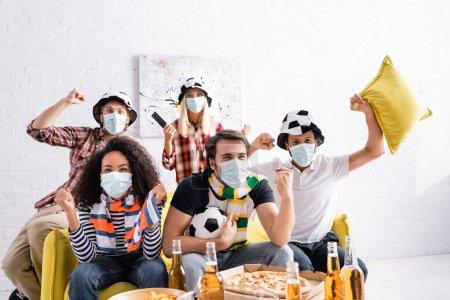 Photo pour Excités amis multiethniques dans des masques médicaux et chapeaux fans de football regarder le championnat à la maison - image libre de droit