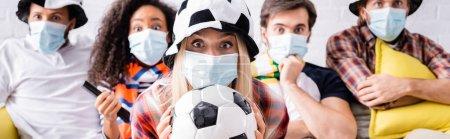 Photo pour Femme dans le chapeau de fan de football tenant ballon de football près choqué amis multiculturels dans des masques médicaux sur fond flou, bannière - image libre de droit