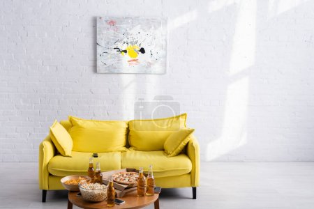 Photo pour Spacieux salon avec canapé jaune, photo sur mur blanc, table avec délicieuse pizza, bière, chips et pop-corn dans des bols - image libre de droit