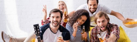 Photo for Smiling woman showing victory gesture near excited friends holding beer during party, banner - Royalty Free Image