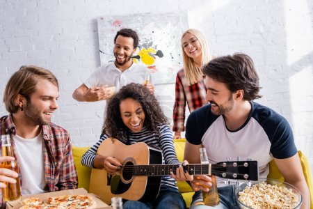 Photo for African american woman laughing while playing acoustic guitar to multiethnic friends during party - Royalty Free Image