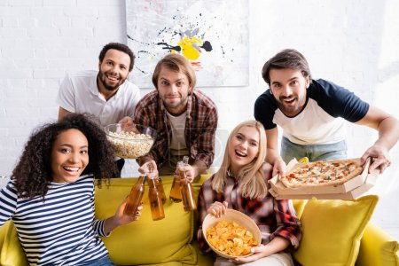cheerful multicultural friend with beer, pizza and snacks looking at camera during party
