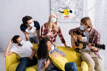 young man playing acoustic guitar to multicultural friends in medical masks sitting on sofa during party