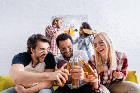 Photo pour Homme excité hurlant tout en cliquetis bouteilles de bière avec des amis multiculturels avec des visages peints - image libre de droit
