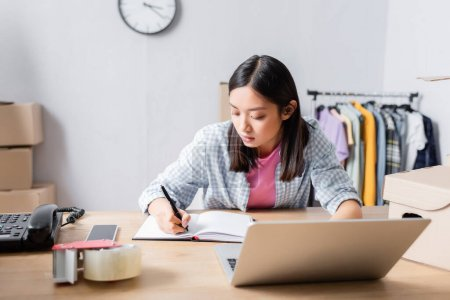 Brunette asian volunteer writing in notebook while sitting at desk with devices in charity office