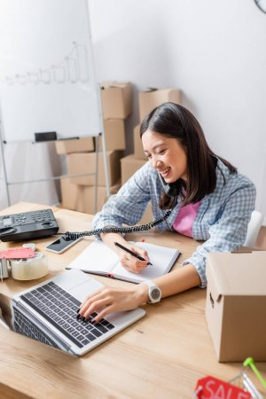 Photo for Smiling asian volunteer with pen, talking on telephone while typing on laptop at desk with carton box in charity center - Royalty Free Image