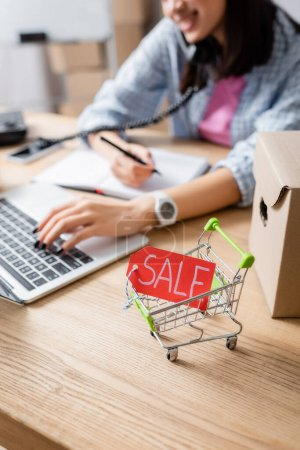Close up view of price tag with sale lettering in shopping cart near carton box on desk with blurred woman on background