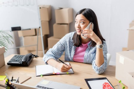 Positive asian volunteer with pen looking away while talking on smartphone at desk with notebook, devices and carton boxes