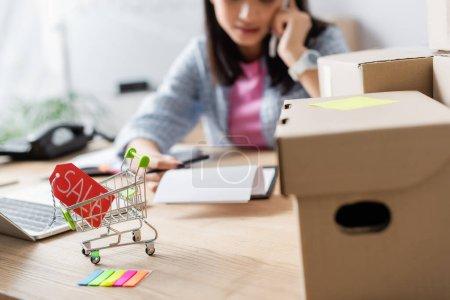 Photo pour Vue rapprochée de l'étiquette de prix avec lettrage de vente dans le panier près des boîtes en carton sur le bureau avec femme floue sur le fond - image libre de droit