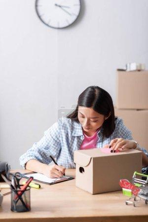 Photo pour Positif asiatique bénévole écriture sur presse-papiers tout en étant assis au bureau avec boîte en carton dans le centre de bienfaisance sur fond flou - image libre de droit