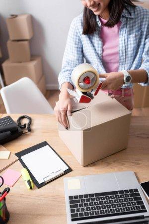 Photo pour Vue recadrée de la femme avec distributeur de scotch boîte en carton de fermeture sur le bureau avec presse-papiers et dispositifs sur fond flou - image libre de droit